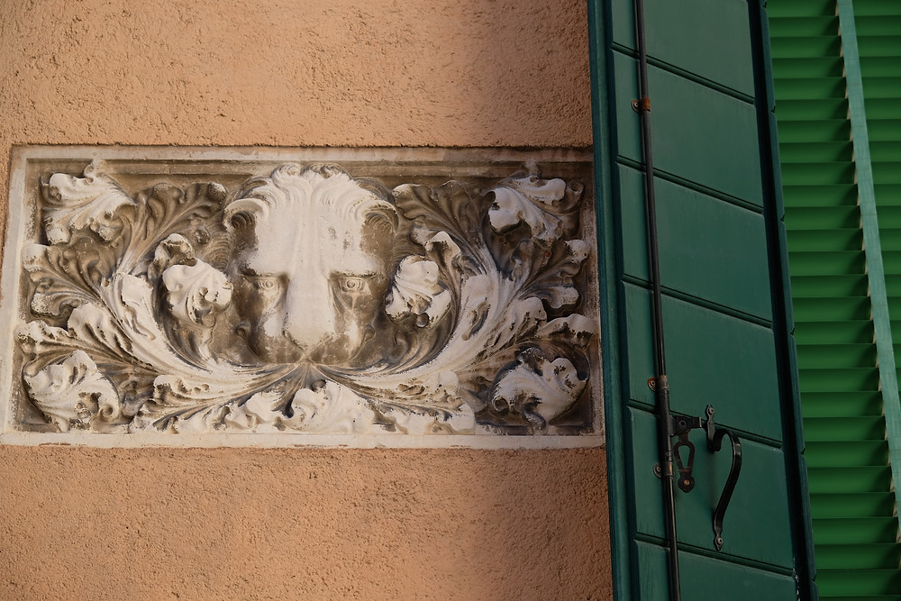 lion in facade of home with green shutter