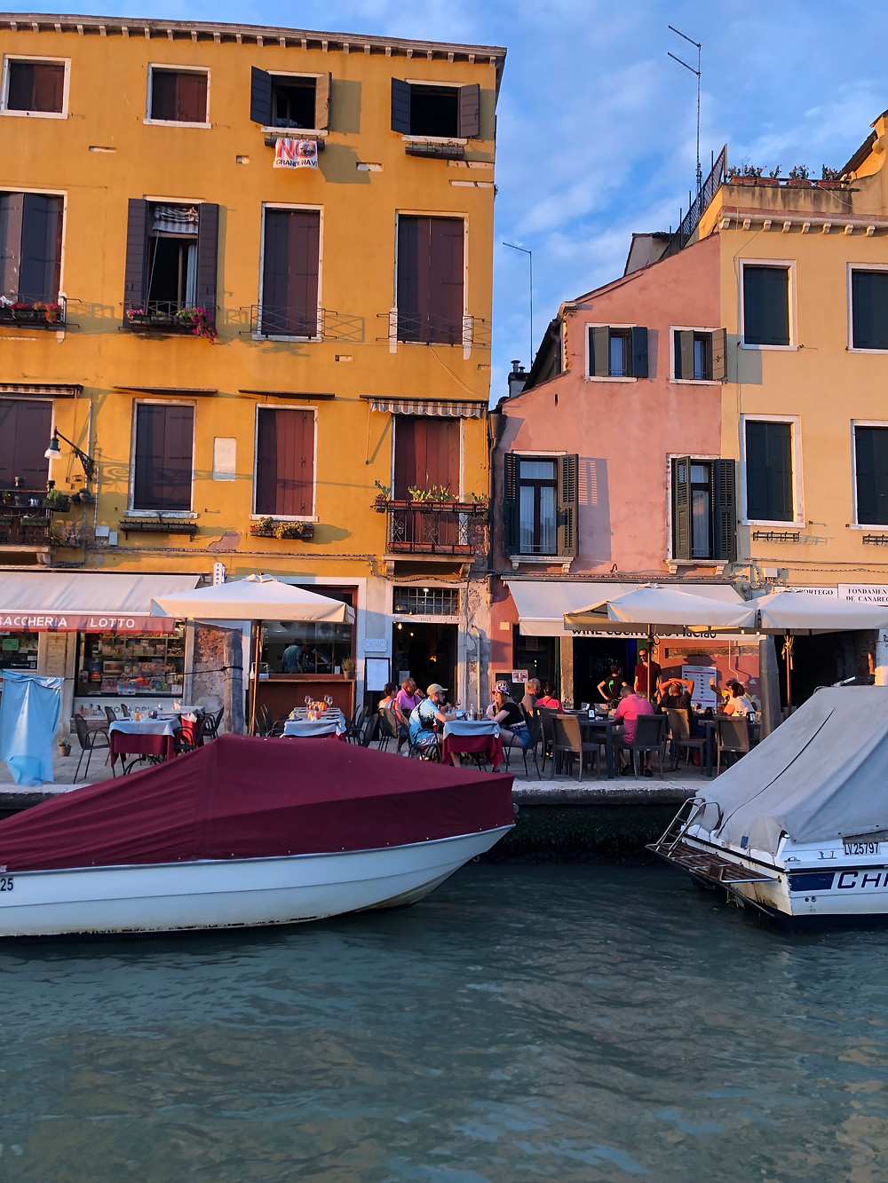 yellow building with red shutters along canal in Venice with boats and people eating at restaurants under umbrellas waterside