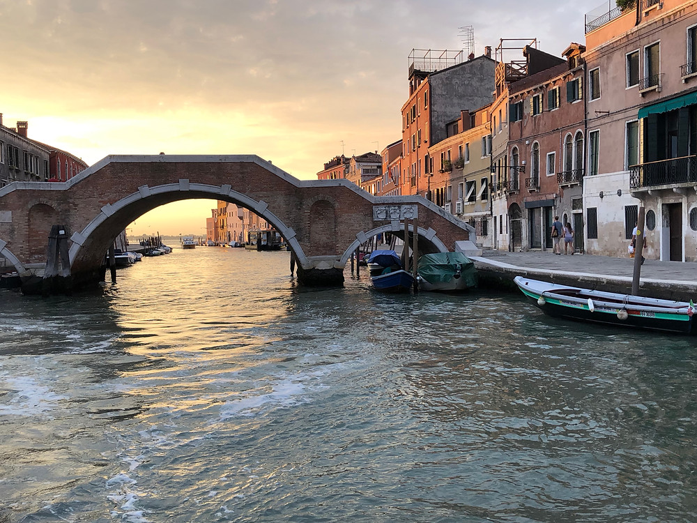 sunset across water and through bridge from a vaporetto boat in Venice