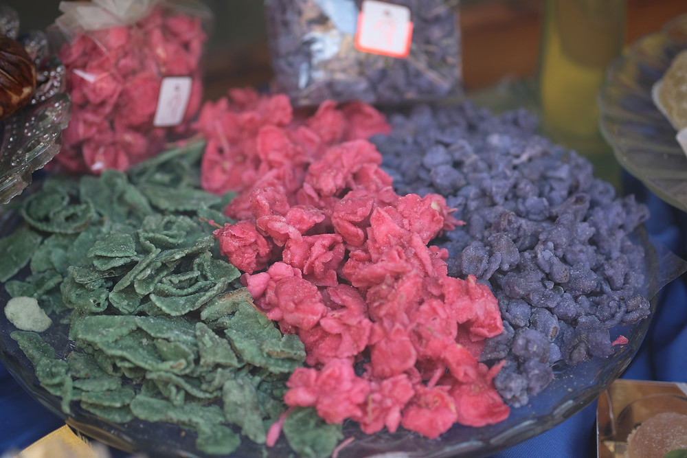 large bowl of pink, green and purple candied violets in a window