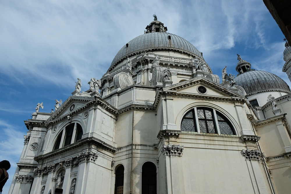 large ornate cathedral from the outside with many statues around the top and blue sky, in Venice