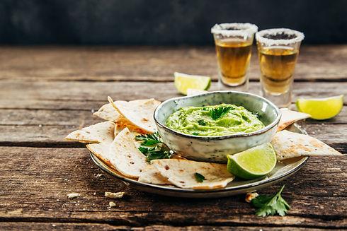 Nachos on plate and avocado sauce and te