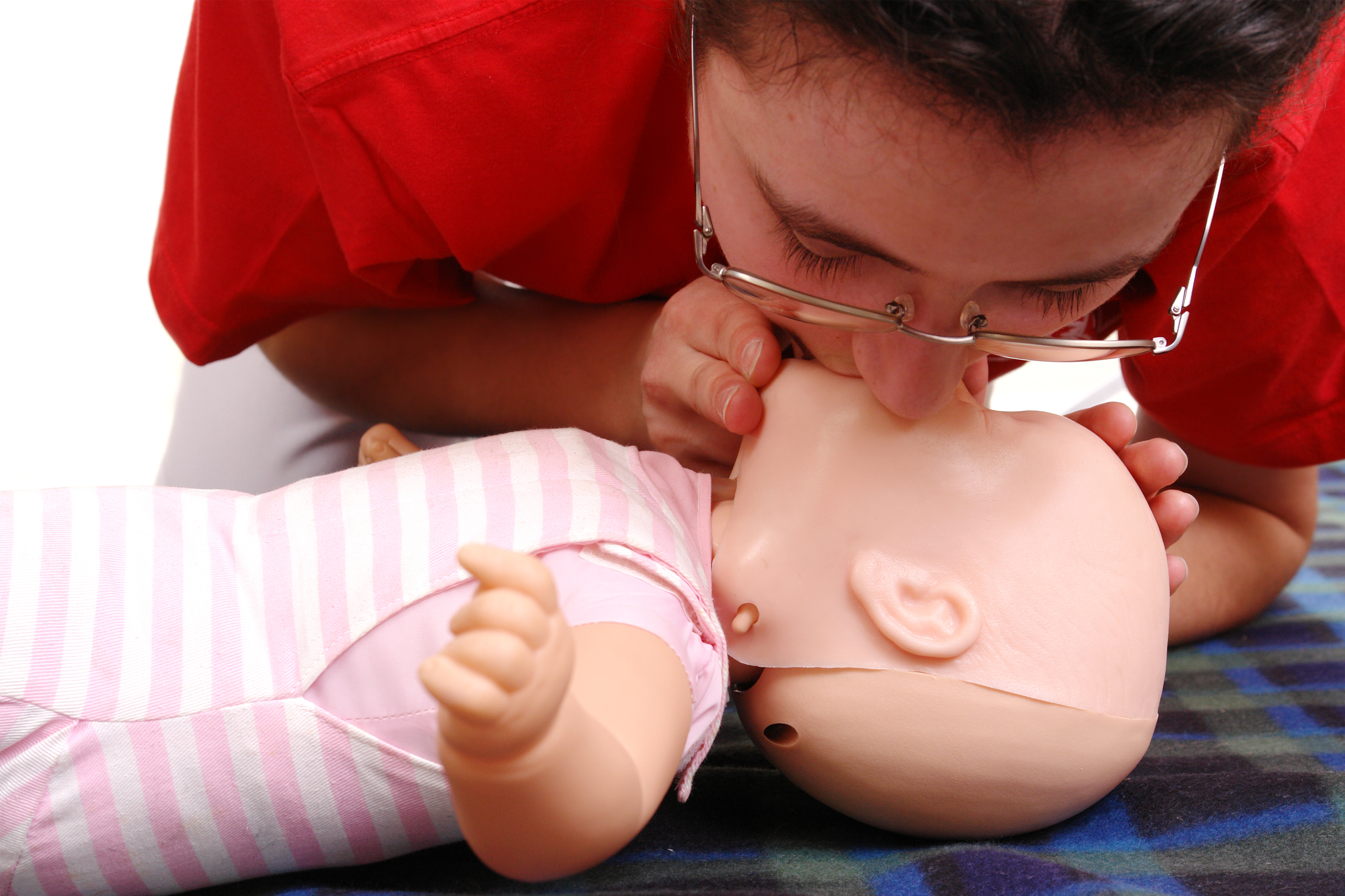 Infant dummy first aid demonstration series - first aid instructor demonstrating artificial respirat