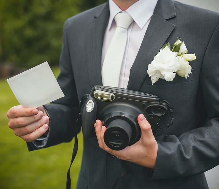 part-of-groom-with-retro-camera-and-empt