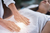 Female therapist performing Reiki therapy treatment holding hands over woman's stomach. Al