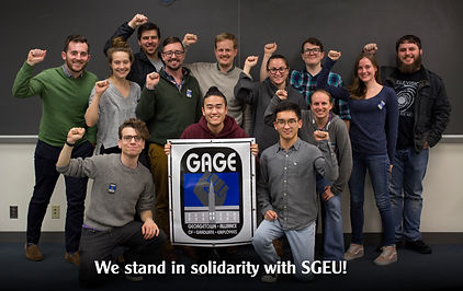 13 people raising their fists behind a poster featuring GAGE logo.  Text at bottom of image reads 'We stand in soldairty wit SGEU!'