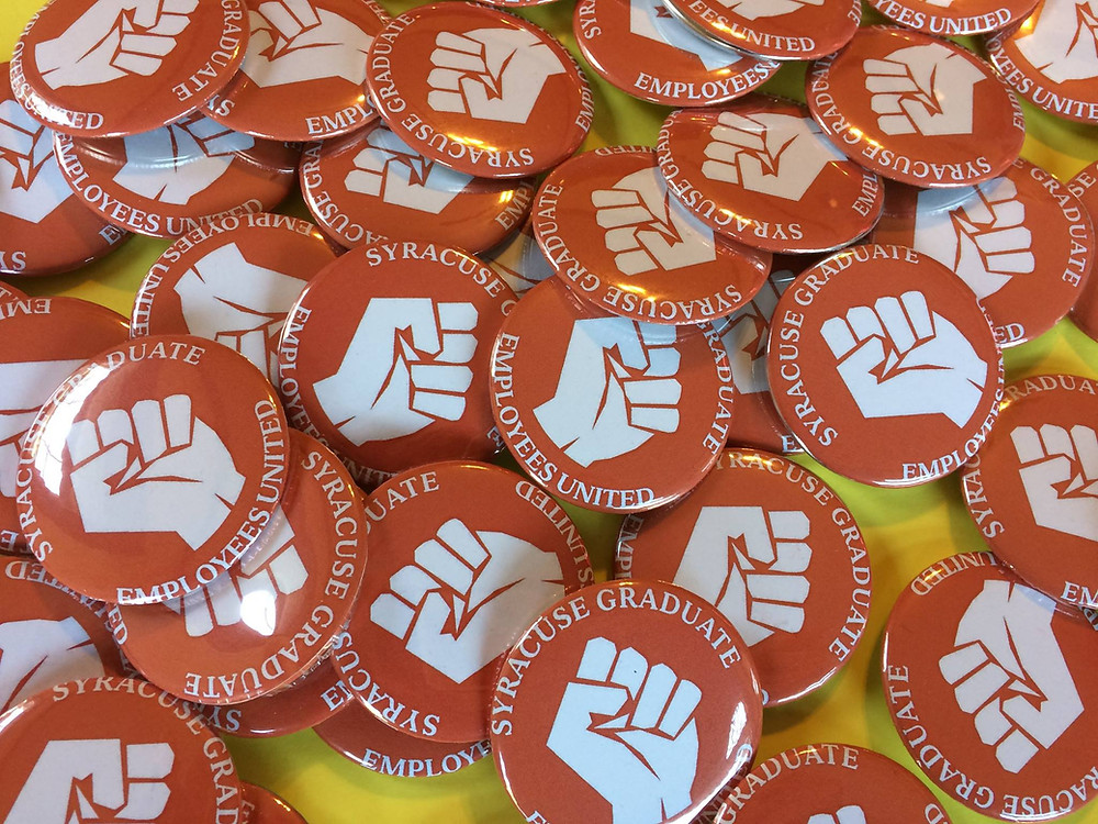 a pile of orange-colored buttons with 'Syracuse Graduate Employees United' along the border and a fist in the center printed in white