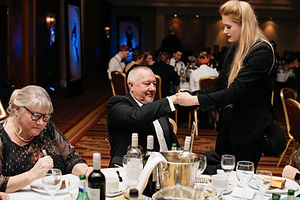 A female magician perfoms a closeup magic trick for a table at an event