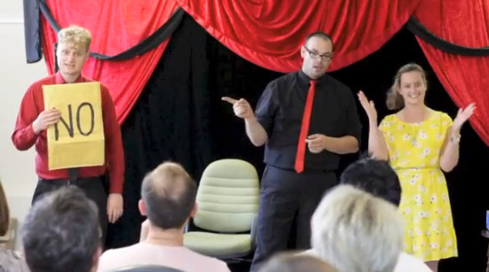 magicians perform stage magic for a women in a yellow dress at a tea building event