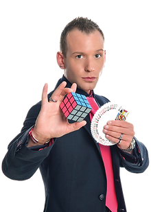a slightly unusual magic entertainer poses with a rubix cube and playing cards