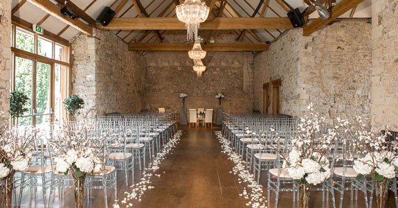a brick wedding venue with chandeliers, seats and an alter