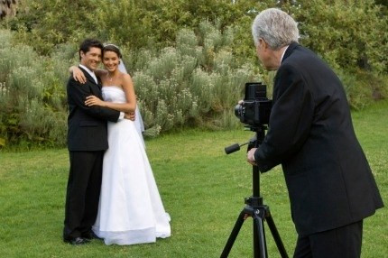 photographer taking a picture of a happy bride in a white wedding dress and groom in black suit