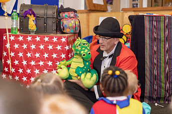 Entertainer showing the kids a dinosaur puppet at one of our showman themed partys