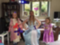 Entertaier dressed as Elsa from frozen posing with 2 princess constumed children