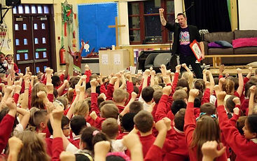Entertainer gets children to throw hands in the air while performing his show at a primary school