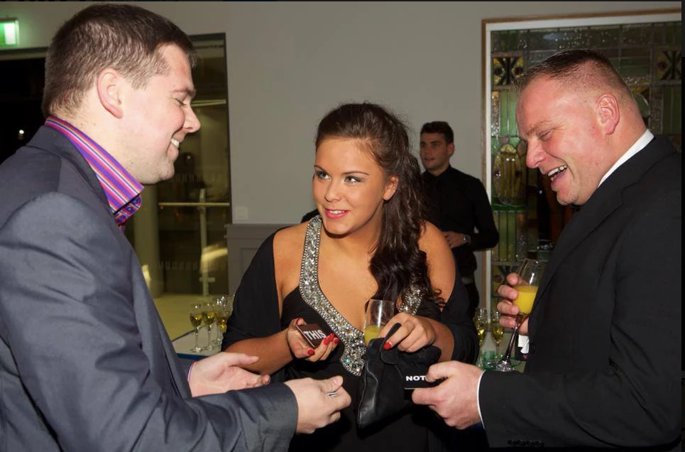 magician in a suit laughing and joking while performing a trick for a couple at an event