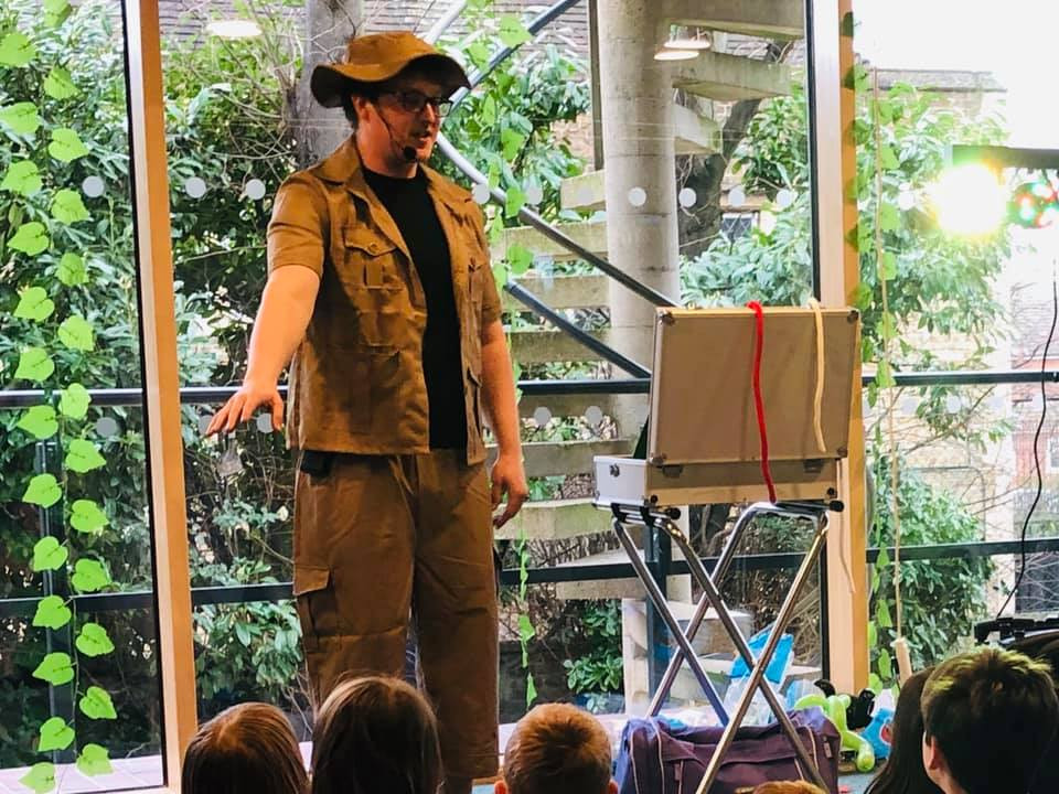 Non stop kids entertainer performs a show at a dinosaur themed party