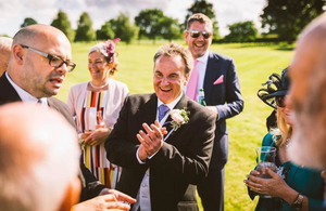 a comedy magician performs some funny magic which leaves group at a wedding smiling & aughing