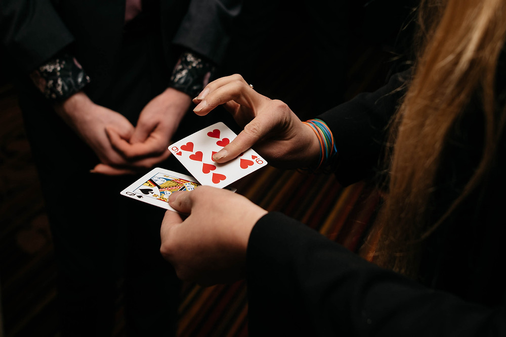 magician performs close up magic at an event using a queen and hearts set of cards