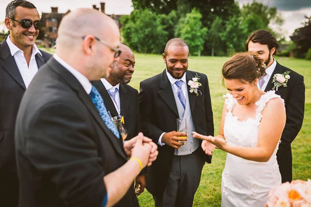 A magician entertainer performs some close up magic for a bride at a wedding event