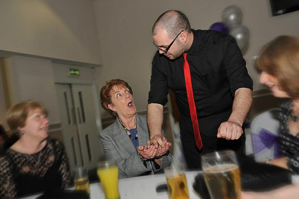 a slightly unusual magician performs close up magic at a private party event
