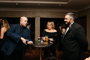 a close up magician entertainer performs for two guests at a private party.