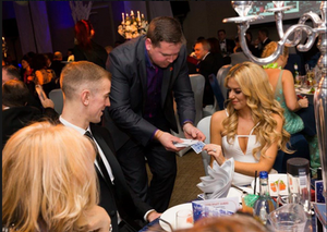 A Slightly Unusual entertainer performs some close up table magic for ex Man City footballer Joe Hart and his wife