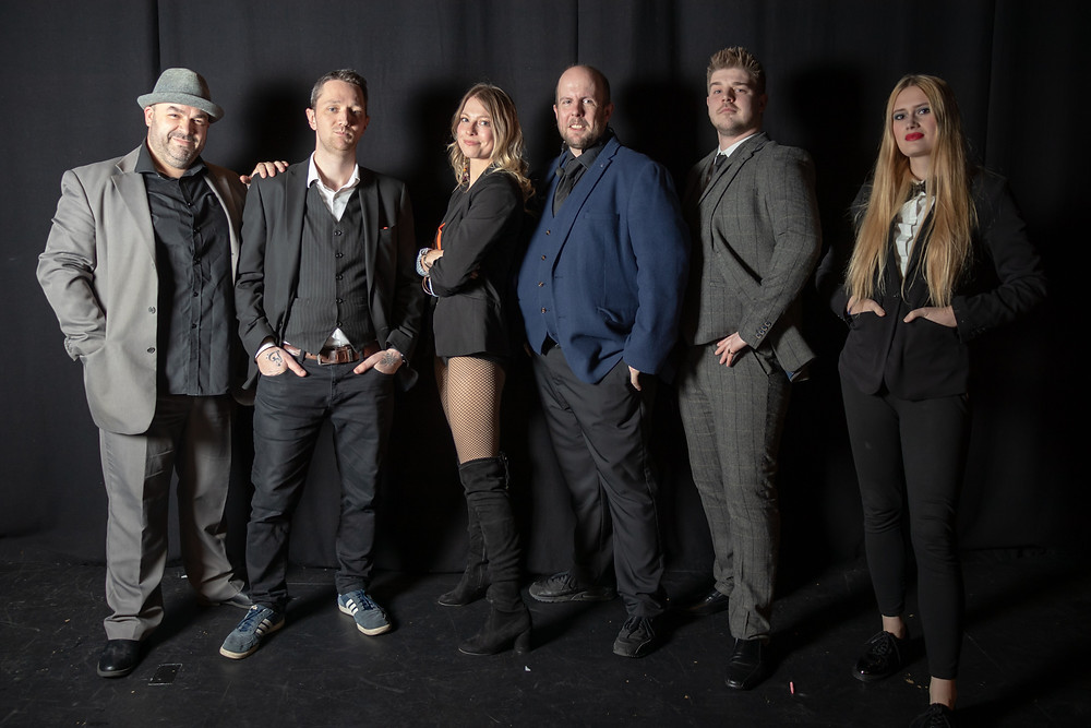 A team of magicians, entertainers and illusionists for slightly unusual pose for the camera at a photoshoot