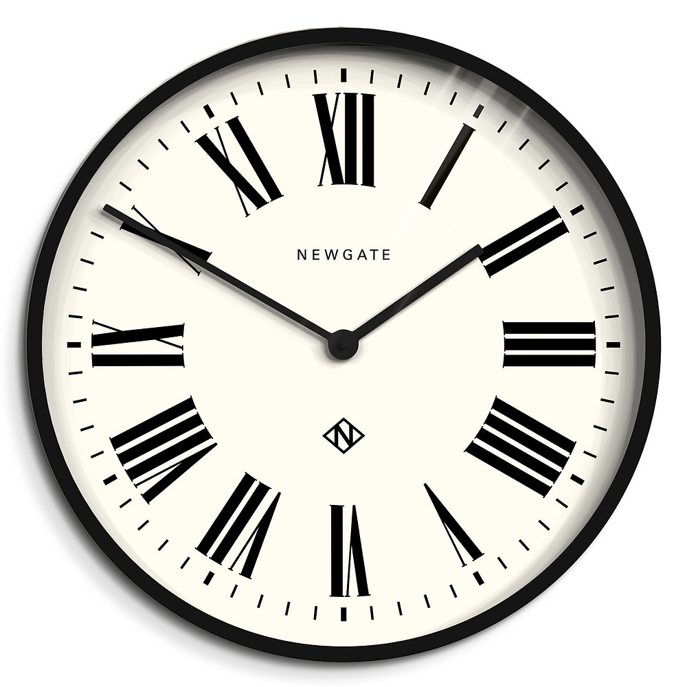 a cream coloured clock with  black roman numerals with clock time being 10 to 2