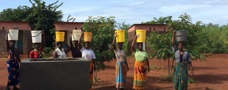 ladies bringing water for cement