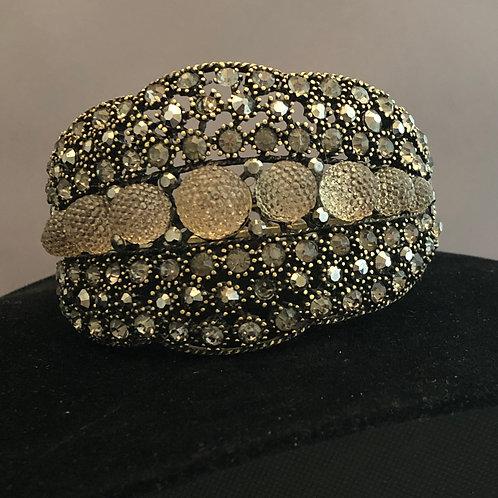 Black hinged bracelet with goldish stones