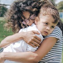 Mum cuddling toddler