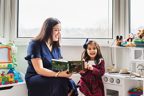 Mother reading a book to her daughter during an at home family photoshoot in North London. Natalie Avery Photography.