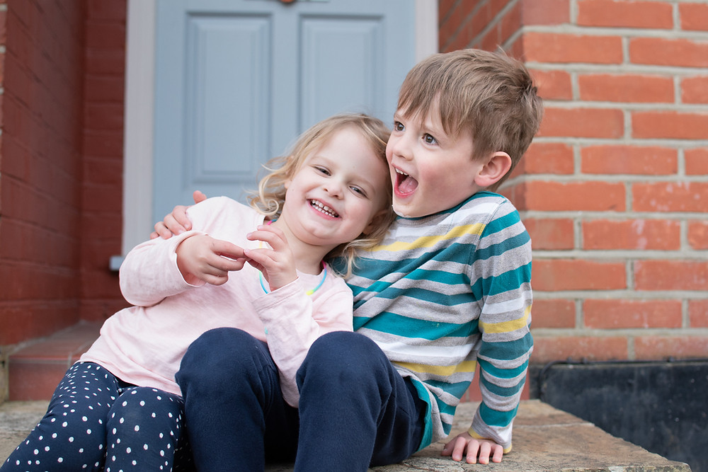 Children laughing and posing for doorstep portrait taken by Natalie Avery Photography.