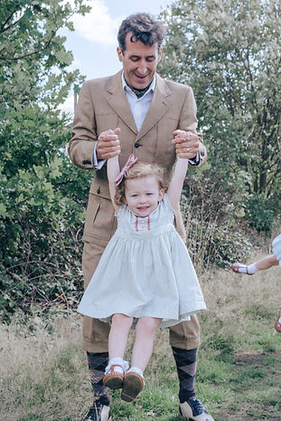 Father swinging daughter by arms taken during outdoor family photoshoot by Natalie Avery Photography
