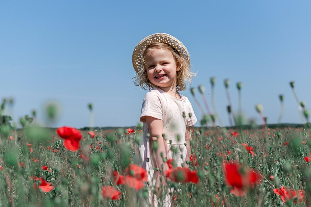 Girl having photo taken in Poppy Field. Taken by Natalie Avery Photography, Family Photographer North London