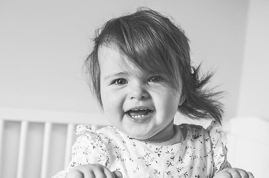 At home picture of a toddler smiling at parents. Family and Newborn Photography North London.