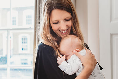 Mother smiling at baby during newborn baby photography in North London