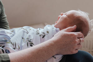 Newborn yawning in mothers arms during at home newborn photoshoot