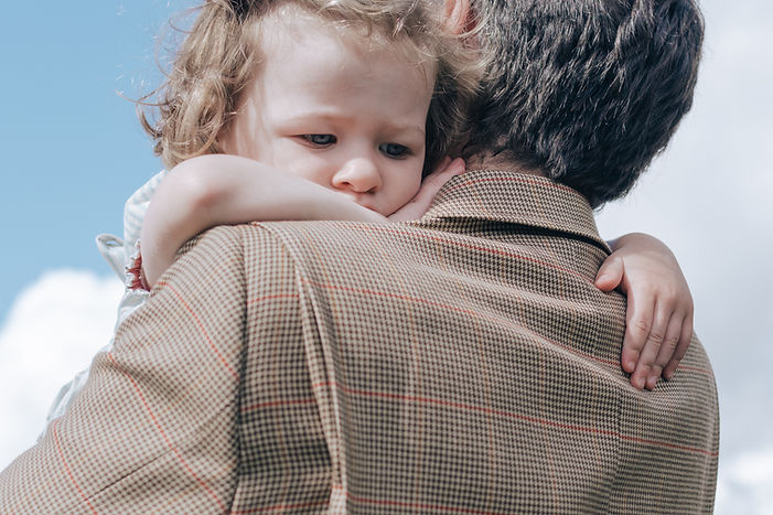 Daughter looking comforted while being carried by Father during family photoshoot North London.