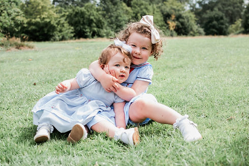 Siblings cuddling during an outdoor family photography in London with Natalie Avery Photography.