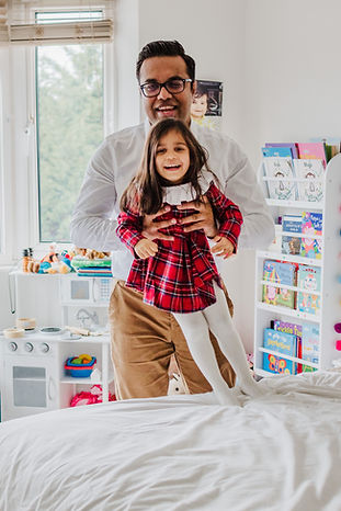 Father throwing daughter on the bed during at home lifestyle family photoshoot in Whetstone