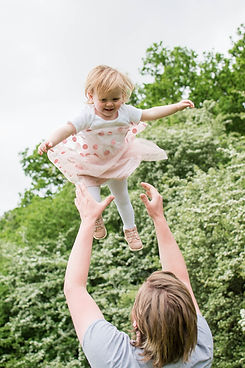 Father throwing little girl in the air during a outdoor family photoshoot.  Family Photography in London.