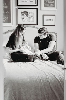 New parents on bed with newborn baby