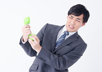 電話によるクレームを受ける若いビジネスマン