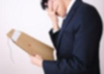 書類を手に思い悩むビジネスマン