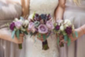 bride with her bridesmaids holding weddi