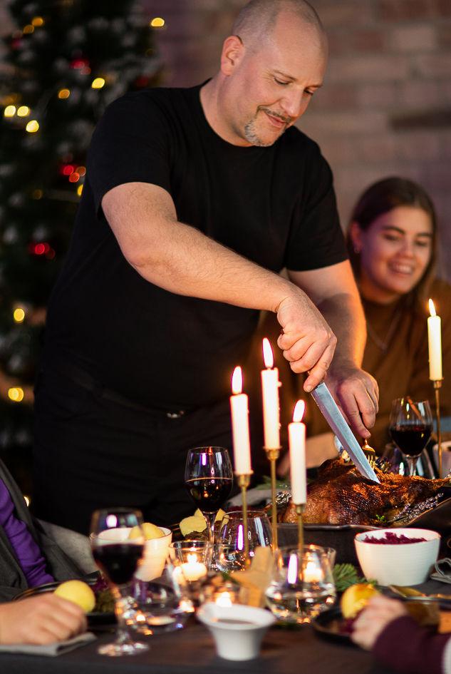 Familie sitzt am Tisch, während die Weihnachtsgans angeschnitten wird