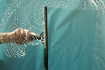 A cleaner uses a squeegee to clean a window.