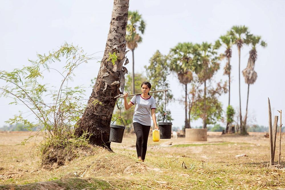 Nuori nainen kantaa vettä ikeellä harteillaan.